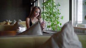 Retrato de uma menina loura bonita que senta-se em um café no verão vídeos de arquivo