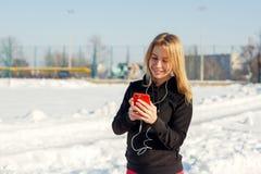 Retrato de uma menina loura bonito que escuta a música ao andar abaixo da rua que guarda um telefone vermelho à disposição A neve fotografia de stock royalty free