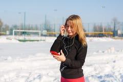 Retrato de uma menina loura bonito que escuta a música ao andar abaixo da rua que guarda um telefone vermelho à disposição A neve imagem de stock royalty free