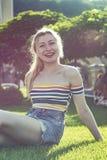 Retrato de uma menina loura nova do sorriso bonito em um parque da cidade, Central Park em um dia ensolarado em uma saia curto Imagem de Stock Royalty Free