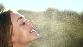 Retrato de uma menina loura nova 'sexy', bonita, sob uma chuva clara do verão, nos raios do sol, em um prado verde A menina filme