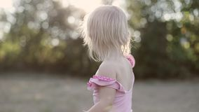 Retrato de uma menina loura pequena suja em um roupa de banho em um parque do verão filme