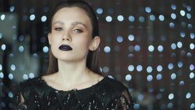 Retrato de uma menina misteriosa e glamoroso com uma aparência incomum no fundo das luzes vídeos de arquivo