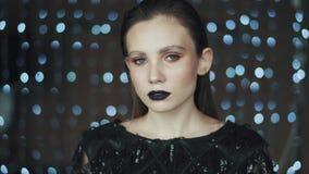 Retrato de uma menina misteriosa e glamoroso com uma aparência incomum no fundo das luzes video estoque