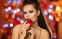 Retrato de uma menina moreno bonita com uma rosa em suas mãos Fotografia de Stock
