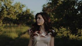 Retrato de uma menina moreno bonita encantador com um sorriso bonito com composição natural na roupa elegante do verão contra video estoque