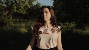 Retrato de uma menina moreno bonita encantador com um sorriso bonito com composição natural na roupa elegante do verão contra vídeos de arquivo