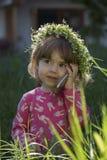Retrato de uma menina na grinalda das flores que fala no telefone celular Imagem de Stock