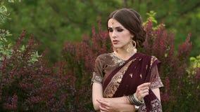 Retrato de uma menina no sari indiano do traje no parque filme