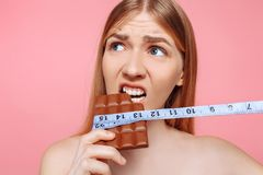Retrato de uma menina pensativa que morde uma barra de chocolate envolvida com uma fita métrica em um fundo cor-de-rosa fotografia de stock