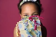 Retrato de uma menina preta nova com um presente Fotografia de Stock Royalty Free