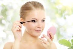 Retrato de uma menina que aplica o mascara foto de stock