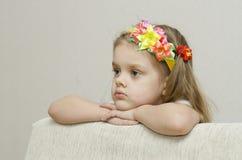 Retrato de uma menina que olhe pensativamente a inclinação esquerda seu cotovelo na parte de trás do sofá Fotografia de Stock