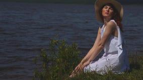 Retrato de uma menina ruivo em um chapéu de palha no fundo de um rio vídeos de arquivo