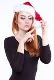 Retrato de uma menina ruivo encantador nova em um chapéu brilhante do Natal, joga com um pompom branco macio Foto de Stock Royalty Free