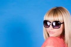 Retrato de uma menina sexual com vidros em um azul Fotos de Stock