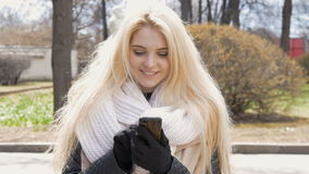 Retrato de uma menina 'sexy' bonita com cabelo louro, sorriso feliz Usa um telefone celular, seletores SMS, comunica-se dentro video estoque