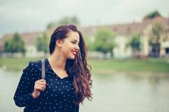 Retrato de uma menina de sorriso alegre com trouxa ao andar fora imagens de stock