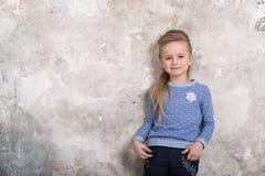 Retrato de uma menina de sorriso atrativa pequena em uma camiseta azul e em cal?as com o cabelo dobrado em seu cabelo contra uma  imagens de stock royalty free