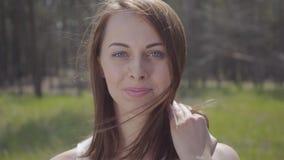 Retrato de uma menina de sorriso bonito bonita com o cabelo que funde no vento Morena macia graciosa lindo dos esportes filme