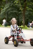 Retrato de uma menina de sorriso do littlel que conduz o carro no divertimento imagem de stock royalty free