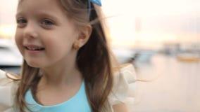 Retrato de uma menina três anos com a curva azul em sua cabeça vídeos de arquivo
