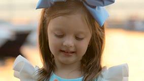 Retrato de uma menina três anos com a curva azul em sua cabeça, suportes perto da água filme