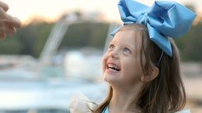 Retrato de uma menina três anos com a curva azul em sua cabeça, suportes perto da água video estoque