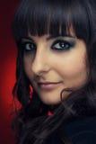 Retrato de uma menina triguenha bonita sobre o vermelho Fotografia de Stock Royalty Free