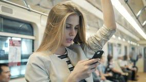 Retrato de uma mensagem de datilografia de sorriso da menina bonita no telefone celular no metro, mulher loura do estudante 'sexy filme