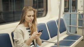 Retrato de uma mensagem de datilografia de sorriso da menina bonita no telefone celular no metro, mulher loura do estudante 'sexy vídeos de arquivo