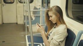 Retrato de uma mensagem de datilografia de sorriso da menina bonita no telefone celular no metro, mulher loura do estudante 'sexy video estoque