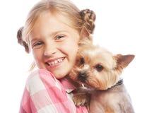 Retrato de uma moça adorável que sorri guardando um cachorrinho bonito fotos de stock royalty free