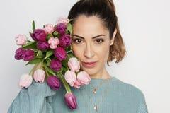 Retrato de uma moça alegre que mantém o ramalhete cor-de-rosa das tulipas isolado sobre o fundo branco imagem de stock royalty free