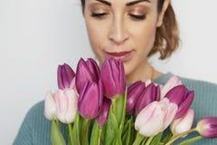 Retrato de uma moça alegre que mantém o ramalhete cor-de-rosa das tulipas isolado sobre o fundo branco fotos de stock royalty free