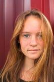 Retrato de uma moça bonita com cabelo longo no fundo da parede metálica de Borgonha Imagens de Stock Royalty Free