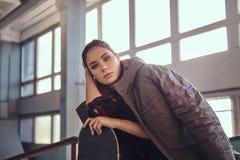 Retrato de uma moça bonita com um revestimento que cobre seus ombros que inclinam-se em um skate e que olham a câmera fotografia de stock