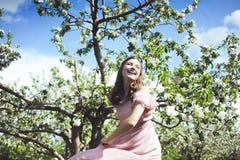 Retrato de uma moça bonita em um vestido do rosa da proposta da noiva do voo em um fundo do campo verde, ri e levanta com a Imagens de Stock Royalty Free