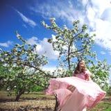 Retrato de uma moça bonita em um vestido do rosa da proposta da noiva do voo em um fundo do campo verde, ri e levanta com a Fotografia de Stock Royalty Free