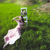 Retrato de uma moça bonita em um vestido do rosa da proposta da noiva do voo em um fundo do campo verde, ri e levanta com a Foto de Stock