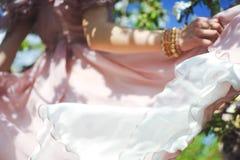 Retrato de uma moça bonita em um vestido do rosa da proposta da noiva do voo em um fundo do campo verde, ri e levanta com a Fotos de Stock Royalty Free