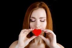 Retrato de uma moça bonita que guarda um coração vermelho Imagem de Stock
