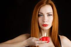 Retrato de uma moça bonita que guarda um coração vermelho Foto de Stock Royalty Free