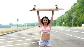 Retrato de uma moça do moderno que sorri com um longboard Movimento lento video estoque