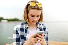 Retrato de uma moça em uma camisa quadriculado que esteja datilografando em um smartphone fotografia de stock royalty free