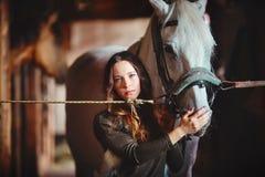 Retrato de uma moça em estábulos de uma vila com um cavalo Vestido no estilo popular foto de stock