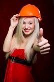 Retrato de uma moça em um terno de Santa e em um capacete da construção fotos de stock royalty free