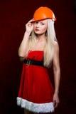 Retrato de uma moça em um terno de Santa e em um capacete da construção imagens de stock royalty free
