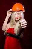 Retrato de uma moça em um terno de Santa e em um capacete da construção imagens de stock