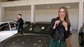 Retrato de uma moça feliz em um concessionário automóvel com chaves a um carro novo filme